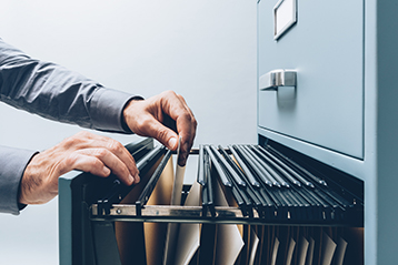 A man searching through a filing cabinet